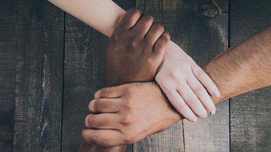 team-hands-linked-together_925x